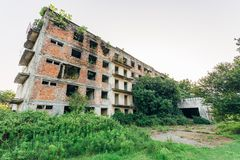 Ruined overgrown apartment house with bullet marks, consequences of war in Abkhazia, green post-apocalyptic concept.  stock image