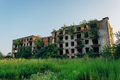 Ruined overgrown apartment house with bullet marks in ghost town, consequences of war in Abkhazia, green post-apocalyptic concept.  stock photo