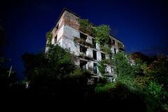 Ruined overgrown apartment house with bullet marks in night ghost town, consequences of war in Abkhazia. Green post-apocalyptic concept royalty free stock photo
