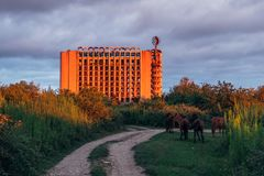 Ruined overgrown sanatorium in evening. Horses graze in the meadow. Consequences of war in Abkhazia. Ruined overgrown sanatorium in evening. Horses graze in the stock photo