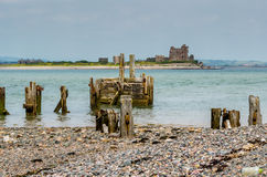 Ruined pier, beach and castle. Ruins of Piel Castle on Piel island, seen from beach with ruins of pier Stock Image