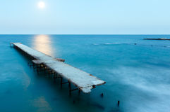 Ruined pier, Moon Path and evening coastline (Bulgaria). Stock Photos