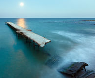 Ruined pier, Moon Path and evening coastline (Bulgaria). Royalty Free Stock Photo