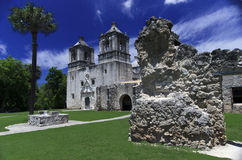 Ruined religion. The active sanctuary on the grounds  of Mission Concepcion  with the ruins of rock and stucco wall with green grass and dark blue sky and wispy Royalty Free Stock Photography