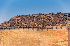 Ruined roof with drooping broken tiles. Roof in disrepair with drooping broken tiles of abandoned country house in Italy Royalty Free Stock Images