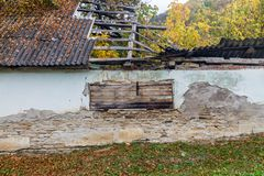Ruined roof of an old house. Closed window with wooden planks royalty free stock image