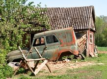 Ruined rusty car standing on green grass near rural buildings. For your design Stock Images