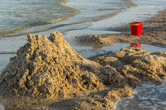 Ruined sand castle and children's bucket Royalty Free Stock Photography