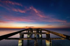 Ruined sea pier in the early morning amidst the dawn stock photo