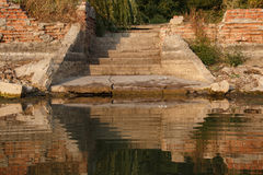 Ruined stairs leading to water. Ruined and abandoned place for swimming. Stairs and platform leading to water with reflection Royalty Free Stock Images