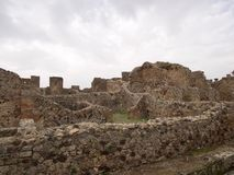Ruined stone walls of ancient building. On archeological site Stock Images
