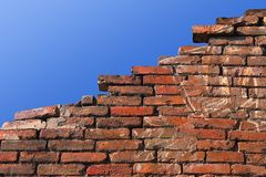 Ruined wall. Old red brick wall against blue sky Royalty Free Stock Photo