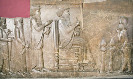 Ruined wall of Persepolis showing king Darius life on relief in National Museum of Iran Royalty Free Stock Image