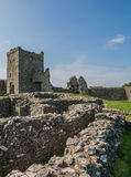 Ruined Welsh Castle. A ruined castle in South West Wales, with low walls and a tower set against a blue, summers sky Stock Images