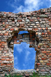 Ruined window. The piece of ruins against a blue sky background. Old brick wall with window and damage, erosion - different colour bricks Stock Photography