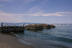 Ruined wooden berth. The old, abandoned pier goes into the sea. Small waves, sandy shore. In the distance, white mountains, hills. Blue water. Bright sky, clouds Stock Photography