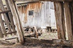 Ruinen der alten Ranch in der Landschaft Defekte hölzerne Scheune und Rad vom Warenkorb stockfotografie