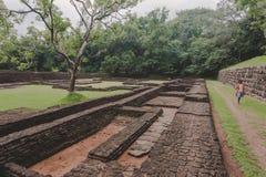 Ruinen der alten Stadt unter Sigiriya-Felsen und lokaler Frau, die auf archäologischen Bereich gehen Der meiste populäre Platz in lizenzfreie stockbilder