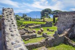 Ruinen der alten Stadt von Pompeji mit den Überresten von Häusern und von Küchengerättöpfen, Vasen Gärten und Vulkan Vesuv im Th stockbilder