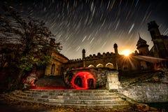 Ruinen des alten Hauses in der sternenklaren Nacht an den startrails und am moonl Lizenzfreie Stockbilder