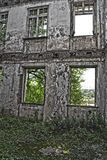 Ruinen des schäbigen Gebäudes abgedeckt durch Vegetation stockfotografie