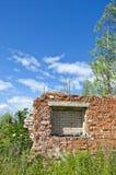 Ruines désolées de maison de brique dans le pré le jour ensoleillé Images libres de droits