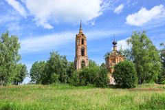 Ruines de belltower et d'églises dans le pré d'été dans la région moyenne de la Russie Images stock