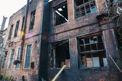 Ruines de maison de brique brûlée après accident de catastrophe du feu Fenêtres cassées avec la cendre Photographie stock libre de droits