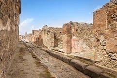 Ruines de Pompeii : rue pavée dans la ville antique détruite par le mont Vésuve photo stock