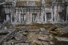 Ruines de temple dans les murs de jungle décorés des ornements et des chiffres Photographie stock