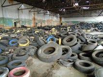 Ruines du bâtiment militaire complètement des déchets illégaux de pneus Image stock
