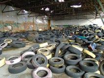Ruines du bâtiment militaire complètement des déchets illégaux de pneus Photos stock