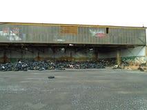Ruines du bâtiment militaire complètement des déchets illégaux de pneus Image libre de droits
