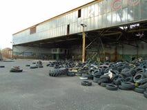 Ruines du bâtiment militaire complètement des déchets illégaux de pneus Photos libres de droits