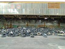 Ruines du bâtiment militaire complètement des déchets illégaux de pneus Images libres de droits