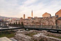 Ruines historiques de Taslihan avec la vieux tour de montre et minaret de la mosquée de Gazi Husrev à images libres de droits