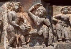 Ruinierte tanzende Leute auf Entlastung des des 12. Jahrhundertshoysaleshwara-Tempels in Halebidu, Indien Stockbild