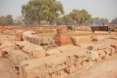 Ruinierte Wände des buddhistischen Tempels im grünen Park mit indischen Touristen Stockfoto
