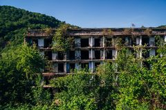 Ruiniertes ?berwuchertes Apartmenthaus in Bergbaustadt des Geistes, Konsequenzen des Krieges in Abchasien, gr?nes nach-apokalypti stockbilder
