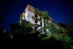 Ruiniertes überwuchertes Apartmenthaus mit Kugelkennzeichen in der Nachtgeisterstadt, Konsequenzen des Krieges in Abchasien lizenzfreies stockfoto