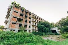 Ruiniertes überwuchertes Apartmenthaus mit Kugelkennzeichen, Konsequenzen des Krieges in Abchasien, grünes Beitrag-apokalyptische stockbild