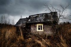 Ruiniertes altes Geisterhaus auf dem leeren Feld mit drastischem blauem Himmel stockfoto