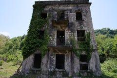 Ruiniertes ?berwuchertes Apartmenthaus in Bergbaustadt des Geistes, Konsequenzen des Krieges in Abchasien, gr?nes nach-apokalypti lizenzfreie stockbilder