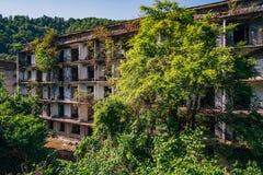 Ruiniertes ?berwuchertes Apartmenthaus in Bergbaustadt des Geistes, Konsequenzen des Krieges in Abchasien, gr?nes nach-apokalypti lizenzfreies stockfoto