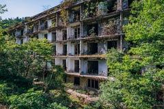 Ruiniertes ?berwuchertes Apartmenthaus in Bergbaustadt des Geistes, Konsequenzen des Krieges in Abchasien, gr?nes nach-apokalypti lizenzfreies stockbild