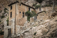 Ruins of an abandoned ancient stone made house built on a mountain slope Stock Images