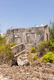 Ruins of an abandoned house covered in shrubs. Concrete grey bro Stock Image