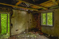 Remains of abandoned damaged and destroyed house interior with collapsed roof and wal. royalty free stock photos