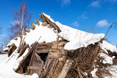 Ruins of abandoned rural house in sunny winter day. In little village in Smolensk region of Russia Stock Photography