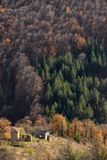 Ruins of abandoned stone houses in a mountain on the Balkans against the backdrop of the autumn forest stock photos